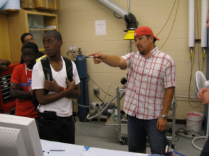 A lab member shows ProCSI 2009 students something in a lab