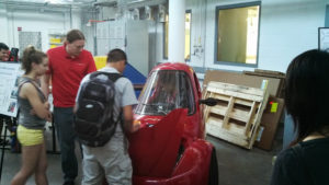 A ProCSI 2013 member checks out what is under the hood of a car