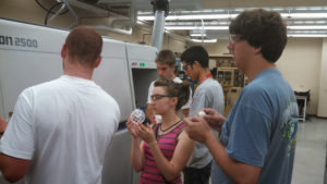 ProCSI 2013 members looking at parts of a machine