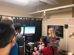 One ProCSI 2018 student tests out a flight simulator as others watch